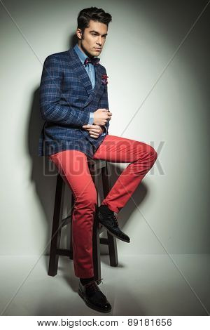Full length picture of a handsome fashion man sitting on a stool while fixing his sleeve.