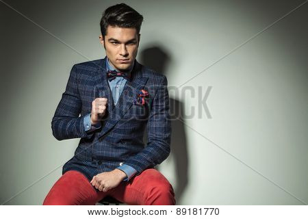 Attractive fashion man fixing his collar while looking away from the camera.