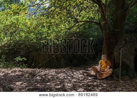 CHIANG DAO, THAILAND, JANUARY 05, 2015: A Buddhist monk leaning back against a tree is meditating in the Chiang Dao mountains in Thailand.