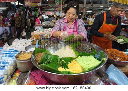 CHIANG MAI,THAILAND,DECEMBER 30,2014: A woman is selling different kind of sticky rices in the Talat Pratu market in Chiang Mai,Thailand