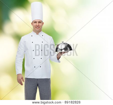 cooking, profession and people concept - happy male chef cook holding cloche over green background