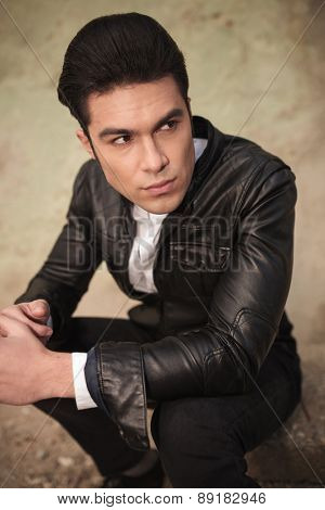 Angle view of an attractive young fashion man sitting while looking away from the camera.