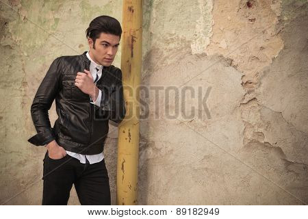 Side view picture of a handsome young fashion man holding one hand in his pocket while leaning on a old yellow pipe.