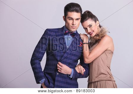 Handsome young fashion man holding his lovers arm while she is leaning on his shoulder.