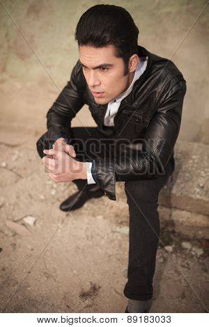 Up view of a handsome casual fashion man sitting near a wall while holding his hands together.