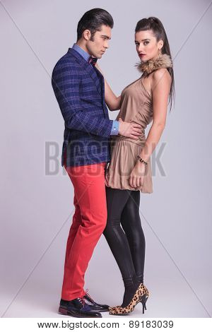 Side view of a handsome young fashion man embracing his girlfriend while she is looking at the camera.