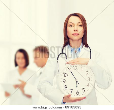 healthcare and medicine concept - calm female doctor with wall clock and stethoscope
