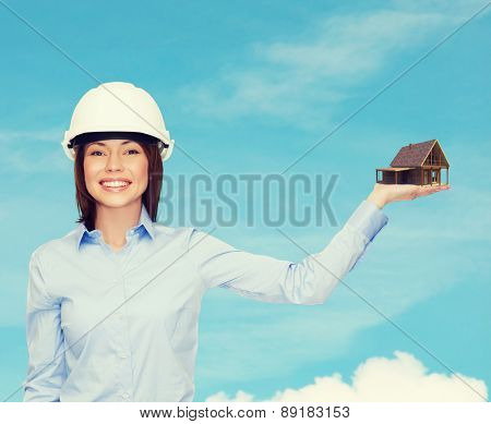 building, developing, advertising and architecture concept - friendly young smiling businesswoman in white helmet holding house on palm