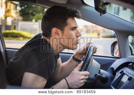 Young Man Leaning Forward on Steering Wheel of Car