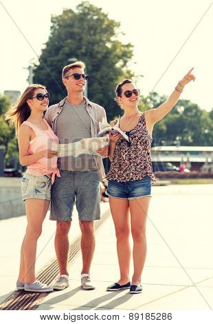 friendship, travel, tourism, vacation and people concept - smiling friends with map and city guide pointing finger outdoors