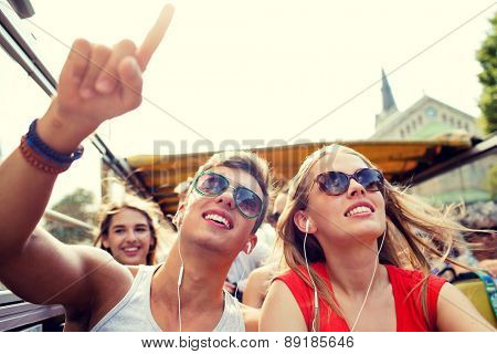 friendship, travel, vacation, summer and people concept - smiling couple with earphones traveling by tour bus and pointing finger