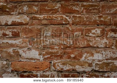 Brick wall of brown color with attritions and cracks
