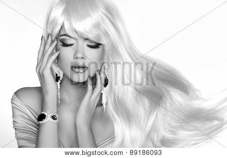 Beautiful Blond Model  With Long Curled Hair. Makeup. Jewelry. Studio Portrait.