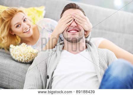 A picture of a woman covering her husband's eyes when watching tv