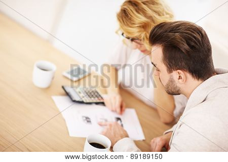 A picture of an adult couple working on documents at home