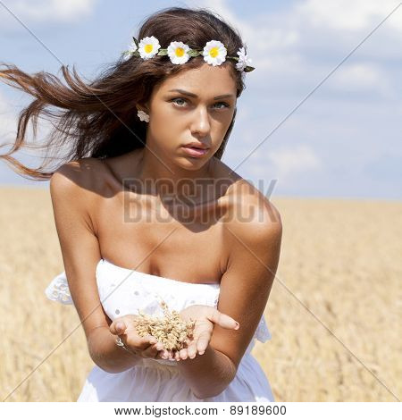Beautiful young woman in white dress on wheat golden field