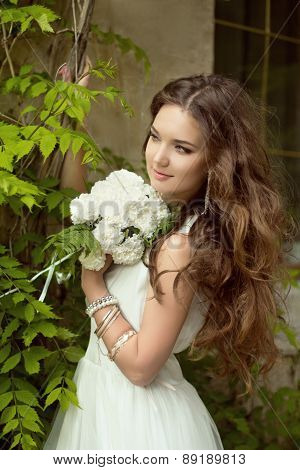 Beautiful Smiling Bride With Wedding Bouquet Of Flowers At Park. Attractive Young Woman Portrait.