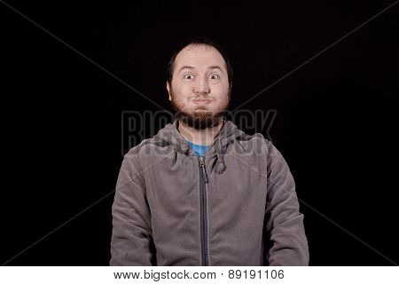 young man making a funny face isolated on black background