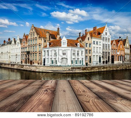 Wooden planks with European view of  Bruges canal and old historic houses of medieval architecture in background. Brugge, Belgium