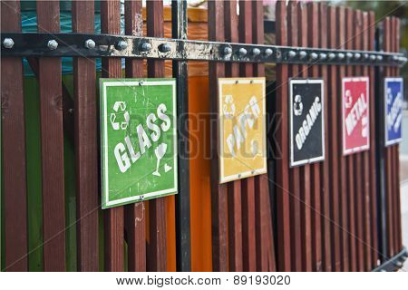 recycle bin place with signs like glass, paper, metal