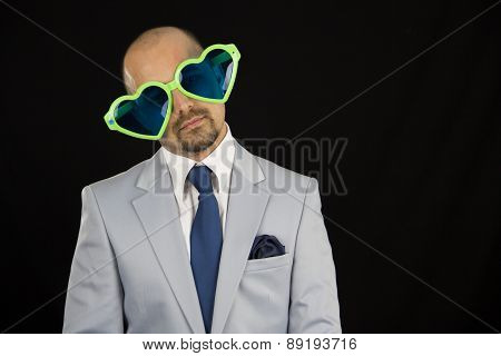 businessman wearing big funky glasses isolated on black background