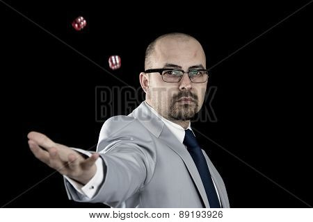 business man throwing dice up in the air isolated on black background