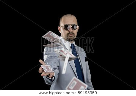 man throwing playing cards up in the air isolated on black background