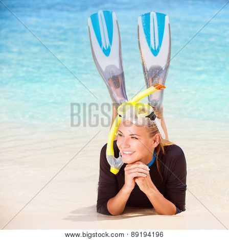Happy diver woman lying down on the beach, wearing flippers and snorkeling mask, having fun on beach resort, enjoy water sport and active summer vacation