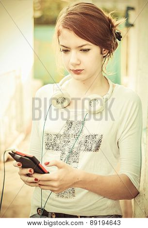 Girl Teenager Listens To Music On The Street In Clear Weather, In Bright Sunlight.the Image Is Tinte
