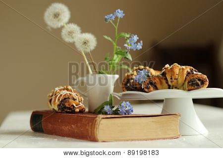 Book with flowers forget-me-not on the vintage book and croissants