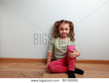 Fun Grimacing Girl Sitting On The Floor And Smiling