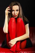 pic of pantyhose  - Sad woman vivid color pantyhose sitting on couch black background - JPG