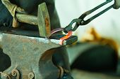 stock photo of blacksmith shop  - Making decorative element in the smithy on the anvil - JPG