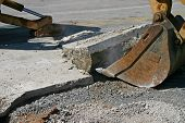 stock photo of backhoe  - the bucket of a backhoe pulling up concrete pavement - JPG