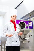 stock photo of ice cream parlor  - Female Chef preparing ice cream with machine in gastronomy parlor kitchen - JPG