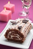 picture of yule  - Yule log cake decorated with chocolate leaves on a Christmas table - JPG