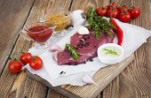 picture of beef shank  - Fresh beef steak with spices vegetables and sauce on a wooden background - JPG