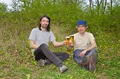 picture of mans-best-friend  - Two happy men talking and drinking beer while sitting in meadow  - JPG