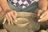 picture of molding clay  - Old Thai male hand carefully using his index finger to finish shaping his clay dish - JPG