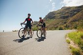stock photo of triathlon  - Two young athletes taking a break from cycling on country road - JPG
