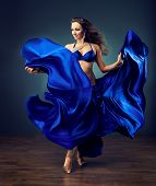 stock photo of belly-dance  - Beautiful girl with great body dances the dance of the belly  in blue shiny costume - JPG