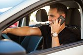 pic of hispanic  - Hispanic young man talking on his phone and driving a car - JPG