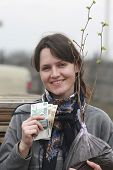 picture of hazelnut tree  - smiling girl holding a tree seedling and banknotes - JPG