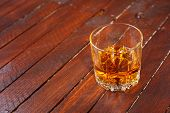 pic of tumblers  - Tumbler glass full of whisky standing on a wooden table - JPG