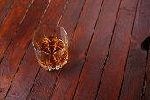 foto of tumbler  - Tumbler glass full of whisky standing on a wooden table - JPG