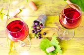pic of wine grapes  - Two glasses of red wine on the background of an old brick wall and grape vines - JPG