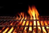 stock photo of flame-grilled  - Empty Flaming Charcoal Grill With Flames Of Fire On Black Background Closeup - JPG