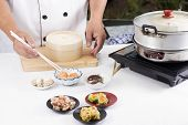 picture of chinese menu  - Chef using chopsticks hold Chinese dumpling  - JPG