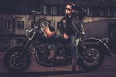 stock photo of carburetor  - Biker and his bobber style motorcycle on a city streets  - JPG