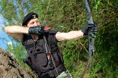 foto of bow arrow  - The soldier shoots with bow and arrow in the forest - JPG